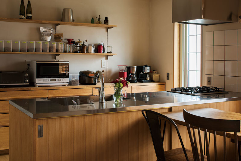 ステンレスとタモ材を用いた造作キッチンには、掃き出し窓を設けて庭へのアクセスと通風を確保