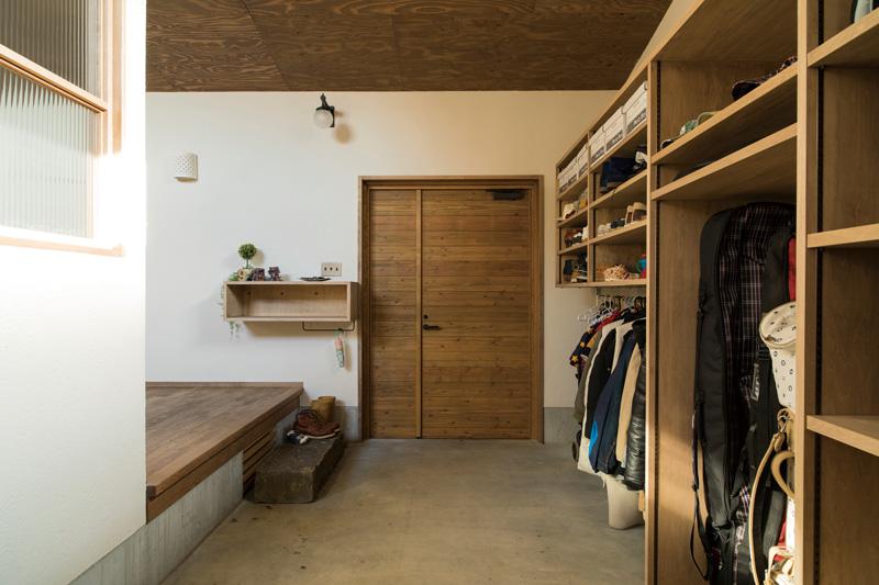 バイクの出入りを考慮して親子ドアを採用した土間玄関。ドアの開け閉めで流れ込む冷気は温水パイプを収めた床下に流れる設計で、室内が寒くなることはない。壁は一面全てが大容量の造作収納