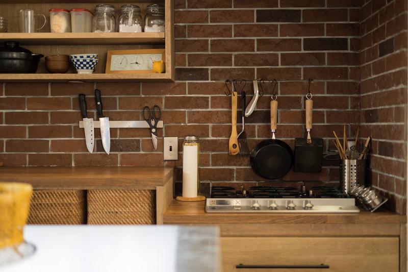 レンガ張りの美しく機能的な造作キッチンは、友人にも大好評。シンク下にはビルトイン型の食器洗い乾燥機も完備し、家事負担を最小限に