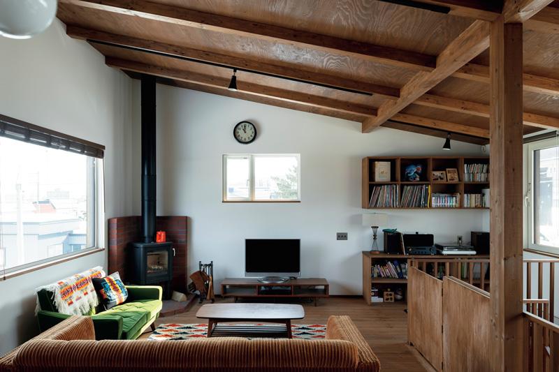 Kさん念願の薪ストーブを設置したリビングは、窓が3方に設けられて明るい雰囲気。冬はテレビ台上の窓からまっすぐに朝日が射し込む。オーディオ収納は、Kさんが所有するソフトや機器に合わせてつくられた