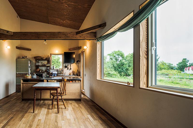 大きな窓から外に広がる菜園の緑が一望できる木と塗り壁のLDK。これからこの空間に合う家具を少しずつそろえていくのも楽しみのひとつ