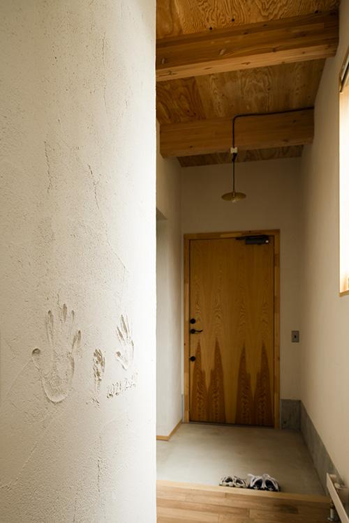 玄関土間と上がり框との段差を少なくし、外から屋内へ緩やかにつながる。玄関ホールの塗り壁には、ご家族の手形が刻まれている